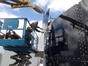 Crew installs glass lined tank panel on water storage tank